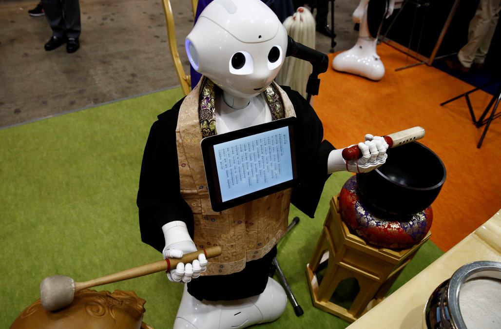 A 'robot priest' wearing a Buddhist robe chants sutras at it beats a wooden fish during its demonstration at Life Ending Industry EXPO 2017 in Tokyo