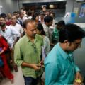 People wait to withdraw and deposit their money at an ATM kiosk in Kolkata