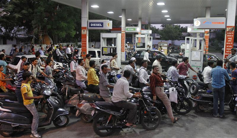 Motorcyclists crowd a fuel station to fill up on petrol in the western Indian city of Ahmedabad