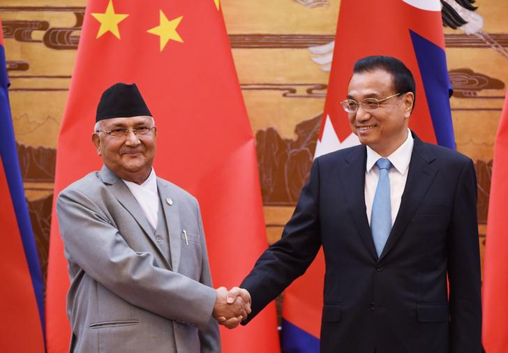 Nepal's Prime Minister K.P. Sharma Oli chats with Chinese Premier Li Keqiang during a signing ceremony at the Great Hall of the People in Beijing