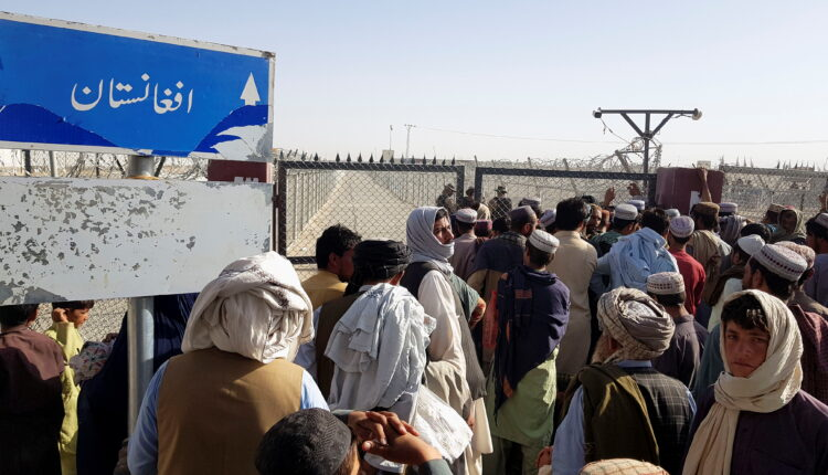 People gather as they wait to cross at the Friendship Gate crossing point in the Pakistan-Afghanistan border town of Chaman