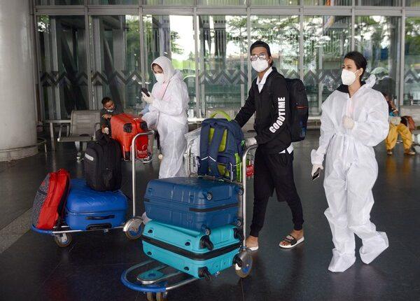 Passengers wearing PPE kit arrive at Netaji Subhash Chandra Bose International Airport