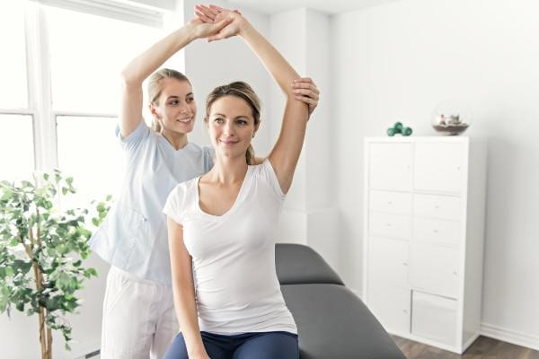 physical-therapist-helping-woman-stretch-her-arm